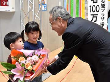 100万人目の利用者となり、理事の寒河江信高畠町長(右)から花束を受け取る「なかよしこども園」の年長児=同町・湯るっと