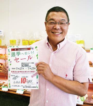 参加店舗に掲示されるチラシを持つ本牧館の黒川社長