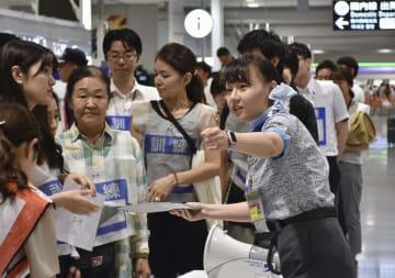 関西空港で行われたBCPに基づく訓練で、利用客の誘導手順を確認する職員(右)=18日午前
