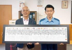 「安全・安心どさんこカルタ一覧パネル」の寄贈を受けた菊池署長(右)と松井代表