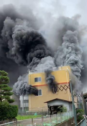 激しく煙を上げる「京都アニメーション」のスタジオ=18日午前10時30分ごろ、京都市伏見区(近隣住民提供)