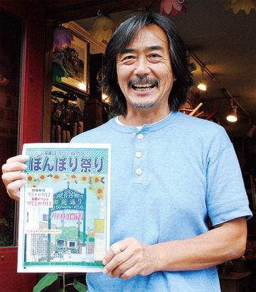「ぼんぼり祭り」のチラシを持つ小嶋会長