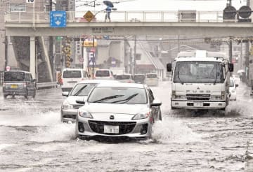 道路が冠水し、水しぶきを上げて走る乗用車やトラック=7月18日午後2時40分ごろ、福井県福井市松本4丁目