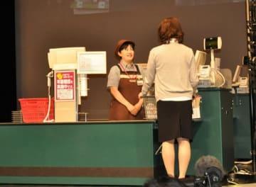 【模範演技でレジ対応をする女性(左)=津市一身田上津部田の県総合文化センターで】
