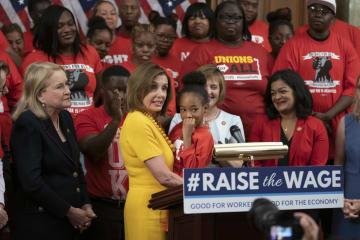 米議会内で7歳の少女を抱き上げるペロシ下院議長(民主党)=18日、ワシントン(AP=共同)