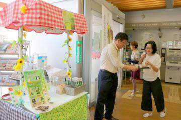 販売ブースのそばでお茶を振る舞う二瀬社長(左)=長崎市、長崎東郵便局
