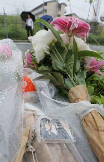 放火で死傷者が出た京都アニメーションのスタジオ近くに置かれた花束と「けいおん」のキーホルダー(19日午前8時45分、京都市伏見区)