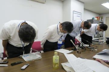記者会見で頭を下げる兵庫県尼崎市教委の関係者ら=19日午後、尼崎市役所