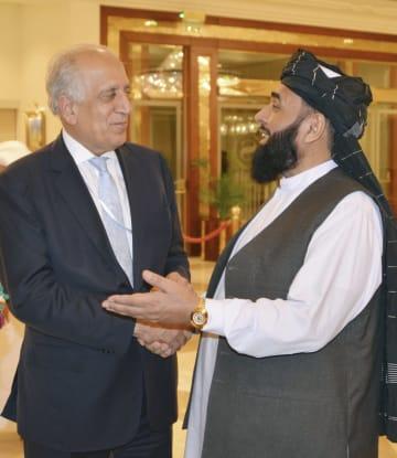 アフガニスタン和平を巡る協議の会場で、言葉を交わす米国のハリルザド・アフガン和平担当特別代表(左)と反政府武装勢力タリバンのメンバー=8日、カタール・ドーハ(共同)