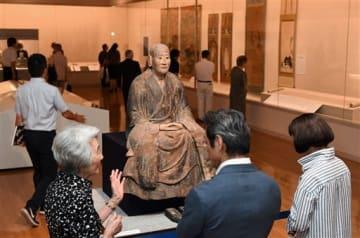 大智禅師の木像(中央)など多数の作品が展示された「菊池川二千年の歴史 菊池一族の戦い」の会場=19日、熊本市中央区の県立美術館本館(上杉勇太)