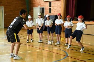 寺島武志選手の投げたボールを蹴り返す児童