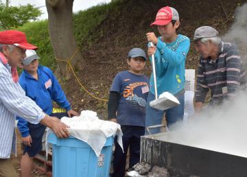 海水を煮詰めてできた塩をすくい上げる児童=鹿嶋市角折