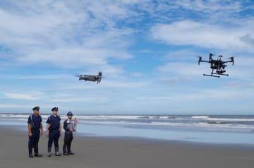 海岸で2台のドローンを飛ばす警備員ら=19日、九十九里町