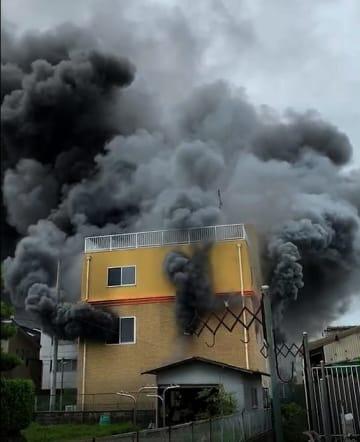 猛煙を上げる京都アニメーションのスタジオ(18日午前10時40分ごろ、京都市伏見区)