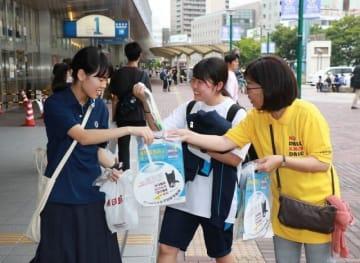 違法薬物に手を出さないよう呼び掛ける岡山市薬剤師会の会員(右)