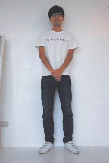 バガスから作られたジーンズを履くさとうきび創生ラボの富井岳さん=19日、浦添市のSHIMA DENIM WORKS