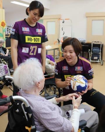 【お年寄りにボールを手渡す選手ら=四日市市笹川のデイサービス「笑門来福ささがわ」で】