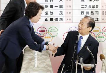 自民党本部の開票センターで、二階幹事長(右)と握手する橋本聖子参院議員会長=21日午後7時59分、東京・永田町