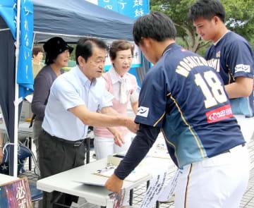 署名したエレファンツの選手に、拉致問題解決の象徴であるブルーリボンを渡す地村さん(左)=7月21日、福井県美浜町の美浜町民広場野球場