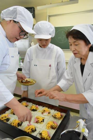 管理栄養士の副島たづ子さん(右)の指導を受けながら盛り付けをする学生=佐賀市の佐賀女子短大