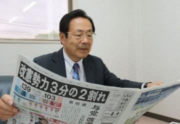 参院選投票から一夜明け、自身の再選を報じる新聞に目を通す石井氏