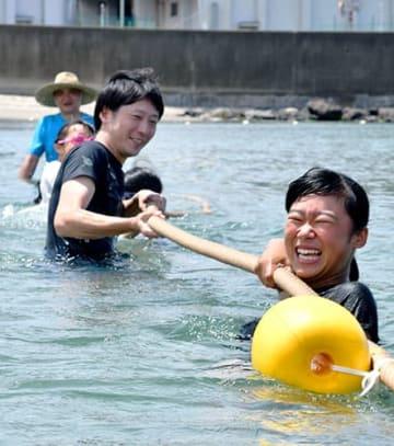 波に体を取られながら力いっぱい綱を引く参加者=酒田市・宮海海水浴場