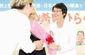 4期目の当選を祝う花束を受け取る紙さん=22日午前7時45分、札幌市東区北12東2の選挙事務所