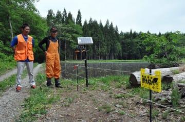 電気柵を設置し、イノシシなどの鳥獣から農作物被害を防いでいる三河尚さん(右)