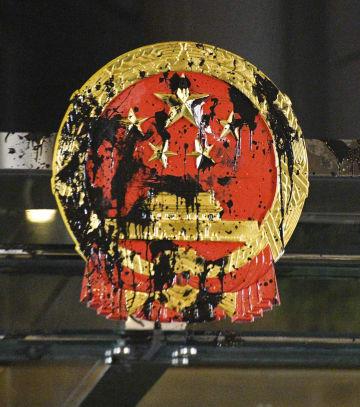 21日、デモ隊の若者らが汚した中国政府の出先機関の国章=香港(共同)
