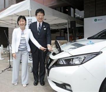 電気自動車(EV)を使って給電のデモンストレーションをする熊本市の大西一史市長(右)と日産自動車の星野朝子副社長=同市
