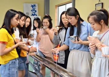 流れてくるそうめんを次々にすくう中国の学生たち=神埼市の井上製麺