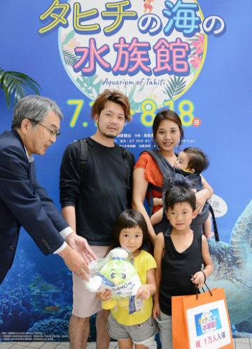 寺谷主幹(左)から記念品を受け取る梶谷さん一家=22日、境港市のSANKO夢みなとタワー