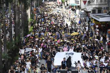 「逃亡犯条例」改正案に反対し、デモ行進する人たち=21日、香港(共同)