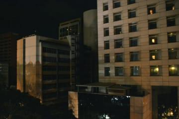 22日、ベネズエラの首都カラカスで停電のため明かりが消えたビル(共同)