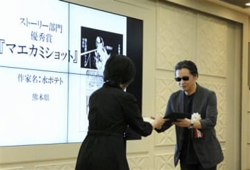 九州まんが賞の授賞式で、特別審査員で漫画家の北条司さん(右)から表彰状を受け取る水ポテトさん=熊本市中央区
