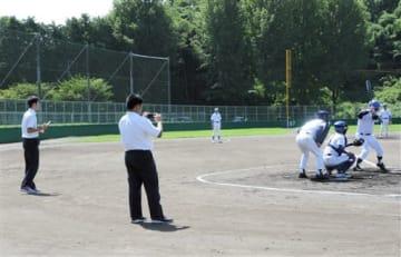 シニアチームのプレーをスマートフォンで撮影する球磨中央高の生徒=人吉市
