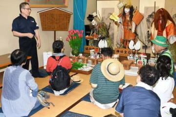 地元の人から笠鉾に飾る人形の説明を聞くお宿巡りの参加者(23日、和歌山県田辺市栄町で)
