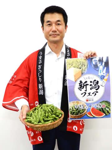 朝採れたばかりの枝豆を手に新潟県フェアをアピールする新潟県農林水産部の白井敏樹さん=23日、さいたま市北区
