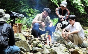 イワナを食べるシーンの撮影に臨む渋川さん(中央)