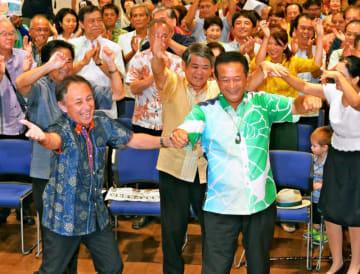 玉城デニー知事(左)ら支持者とカチャーシーを踊り、初当選を喜ぶ高良鉄美氏=21日、那覇市古島・教育福祉会館