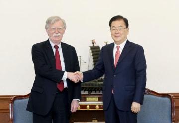 握手するボルトン米大統領補佐官(左)と韓国大統領府の鄭義溶・国家安保室長=24日、ソウル(韓国大統領府提供、聯合=共同)