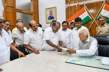 カルナタカ州のバラ知事(手前右)に辞表を提出するクマラスワミ首相=23日、バンガロールで(PTI)