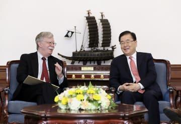 24日、ソウルで会談する韓国大統領府の鄭義溶・国家安保室長(右)とボルトン米大統領補佐官(韓国大統領府提供・共同)