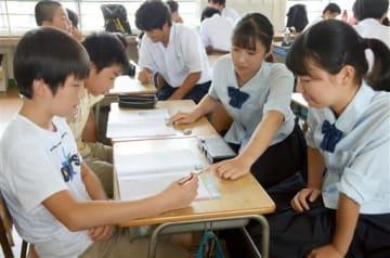 城山小の児童(左側)に勉強を教える熊本西高の生徒たち=熊本市西区