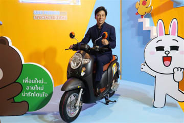 A.P. Honda Co. President Shigeto Kimura poses on a limited edition model of its popular scooter Scoopy i collaboratively designed with messaging app provider Line Corp. at a launch event in Bangkok on July 22.