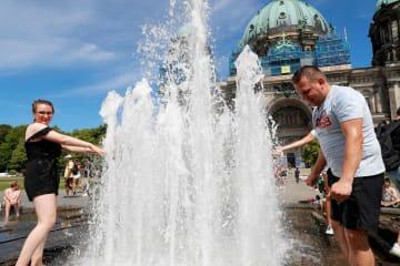 暑さの中、噴水で涼む市民ら=24日、ベルリン(ロイター=共同)