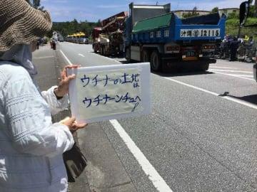 資材搬入するダンプカーを見ながら抗議する女性=25日、名護市辺野古の米軍キャンプ・シュワブゲート前