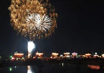 夜空を彩る花火と笠鉾の引きそろえ(24日、和歌山県田辺市の会津橋から撮影)