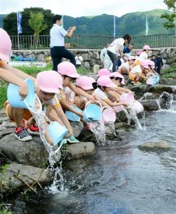 花原川にヤマメの稚魚を放流する園児たち=阿蘇市