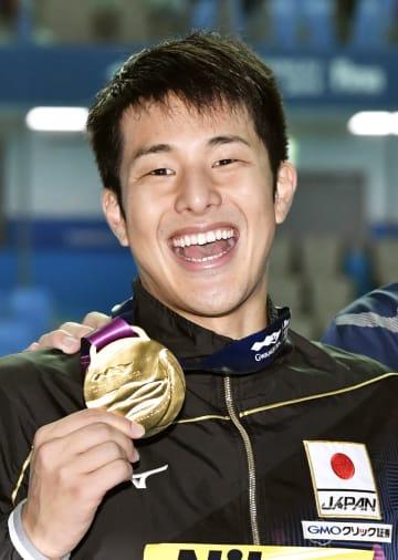 水泳の世界選手権男子200メートル個人メドレーで優勝し、金メダルを手に笑顔の瀬戸大也。東京五輪の代表に決まった=25日、韓国・光州(共同)